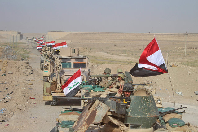 Iraqi government forces are seen near the Falahat village west of Fallujah on June 27, 2016. Iraqi forces took the Islamic State group's last positions in the city of Fallujah on June 26, establishing full control over one of the jihadists' most emblematic bastions after a month-long operation. (Photo by Moadh Al-Dulaimi/AFP Photo)