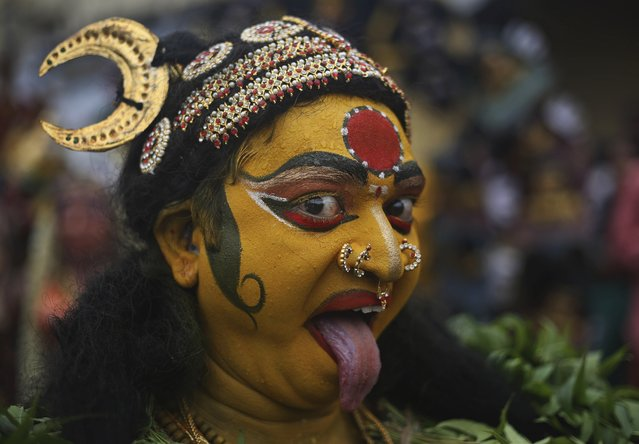 """An Indian artist dressed as Hindu goddess Kali performs during a procession as part of """"Bonalu"""" festivities in Hyderabad, India, Monday, July 21, 2014. Bonalu is a Hindu folk festival of the Telangana State. (Photo by Mahesh Kumar A./AP Photo)"""