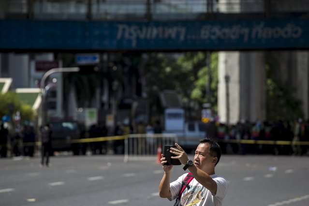 A tourist takes a picture near the site of a deadly blast in central Bangkok, Thailand, August 18, 2015. (Photo by Athit Perawongmetha/Reuters)