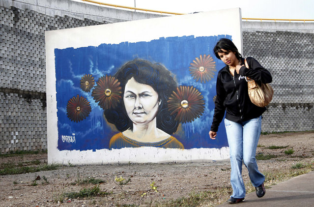 In this Jan. 31, 2017 file photo, a woman walks past a mural of slain environmentalist and indigenous leader Berta Caceres in Tegucigalpa, Honduras. Two European development banks financing construction of a controversial dam project in Honduras are pulling out following the murders of local activists including Caceres, a 2015 winner of the prestigious Goldman Environmental Prize. (Photo by Fernando Antonio/AP Photo)