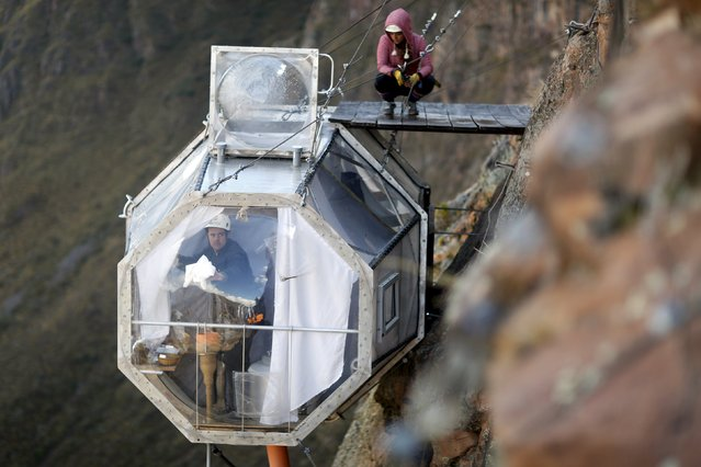 A guest cleans the inside of a sleeping pod at the Skylodge Adventure Suites in the Sacred Valley in Cuzco, Peru, August 14, 2015. (Photo by Pilar Olivares/Reuters)