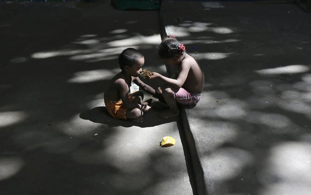 A girl feeds her brother in a slum area under a flyover in Kolkata, India, June 29, 2016. (Photo by Rupak De Chowdhuri/Reuters)