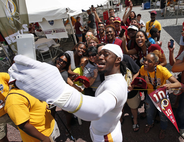 Washington Redskins quarterback Robert Griffin III takes a selfie with a group of fans after practice at the team's NFL football training facility, Monday, July 28, 2014 in Richmond, Va. (Photo by Alex Brandon/AP Photo)