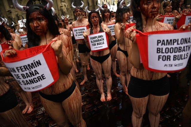 """People cover their bodies with theatrical blood as they hold buckets with slogans to protest against bull runs in front of the City Hall on the eve of the famous San Fermin festival, in Pamplona, northern Spain, Tuesday, July 5, 2016. The festival will begin on July 6 with the """"txupinazo"""" opening ceremony, with people participating in bull runs, music and dance, through the old city. (Photo by Alvaro Barrientos/AP Photo)"""