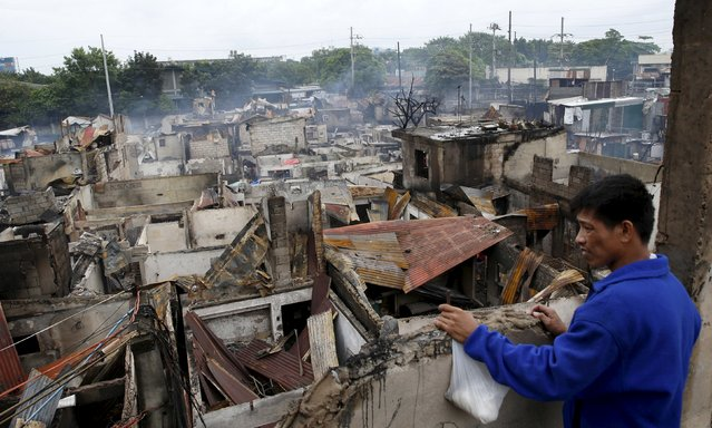A man looks out from a destroyed window at ruins of houses razed by a fire, in Paranaque, Metro Manila in the Philippines August 21, 2015. (Photo by Erik De Castro/Reuters)