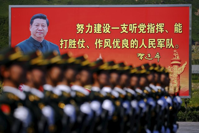 """A picture of Chinese President Xi Jinping is seen on a billboard behind soldiers of China's People's Liberation Army marching during a training session for a military parade to mark the 70th anniversary of the end of World War Two, at a military base in Beijing, China, August 22, 2015. The billboard reads, """"Work hard to build a people's army that is following the party's command, capable of winning wars and maintaining good discipline"""". (Photo by Damir Sagolj/Reuters)"""