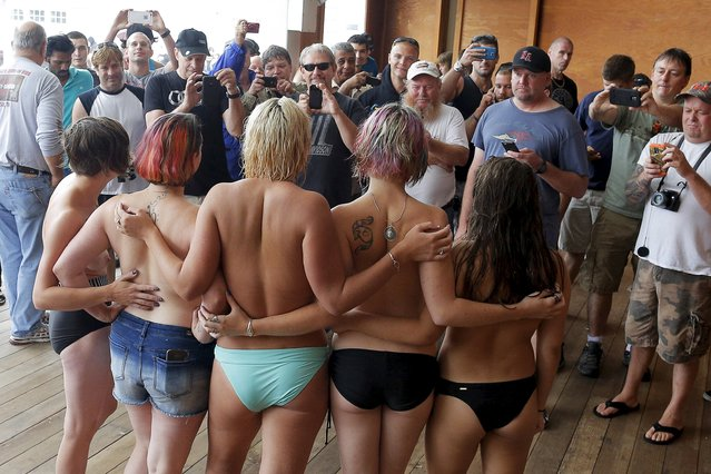 "Topless activists pose for photographs for onlookers during a ""Free the Nipple"" demonstration in Hampton Beach, New Hampshire August 23, 2015. (Photo by Brian Snyder/Reuters)"