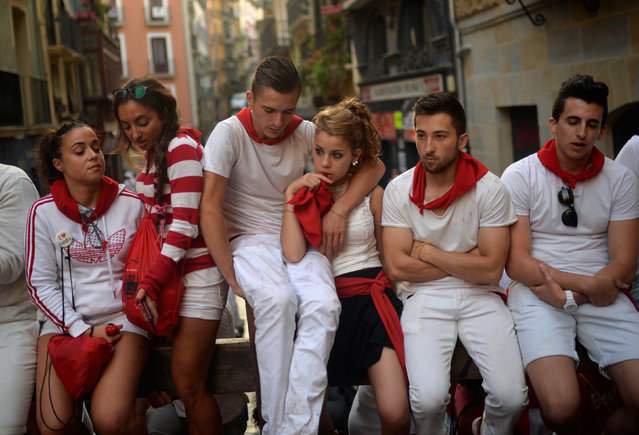 Revellers wait for the fourth running of the bulls at the San Fermin festival in Pamplona, northern Spain, July 10, 201. (Photo by Vincent West/Reuters)
