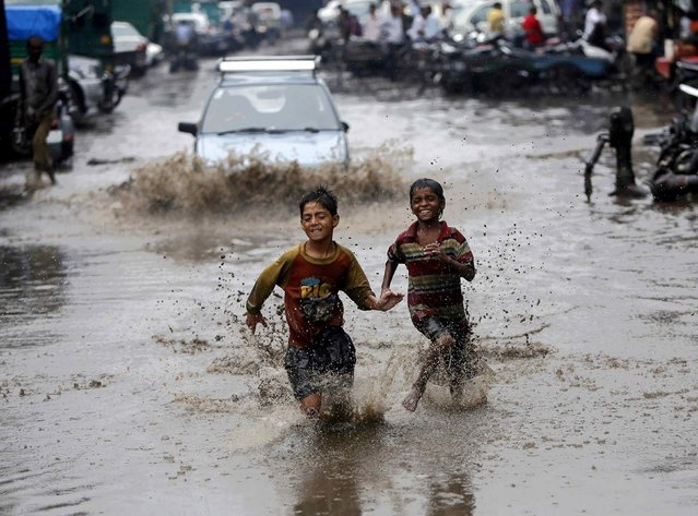 Boys run through a water logged street after heavy monsoon rains in New Delhi August 2, 2014. India's monsoon rains were nine percent below average in the week that ended July 30, the weather office said on Thursday, reflecting a patchy phase after the previous week's surplus downpours. (Photo by Anindito Mukherjee/Reuters)