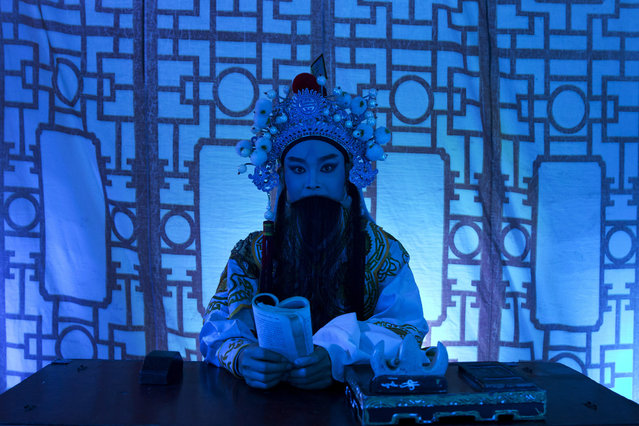 """In this August 30, 2017, photo, a Chinese opera actor performs at a makeshift theater during the """"Hungry Ghost Festival"""" in Hong Kong. (Photo by Kin Cheung/AP Photo)"""