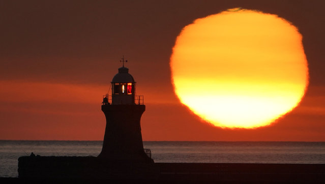 The sun rises over South Shields lighthouse on the north east coast England on December 30, 2019. (Photo by Owen Humphreys/PA Images via Getty Images)