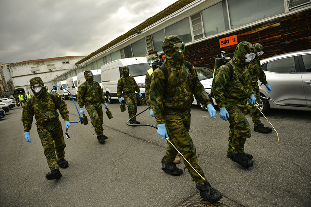 Member of Military Emergency Unit walk with special equipment to disinfect areas to prevent the spread of the coronavirus, arrive at Abando train station, in Bilbao, northern Spain, Monday, March 23, 202. (Photo by Alvaro Barrientos/AP Photo)