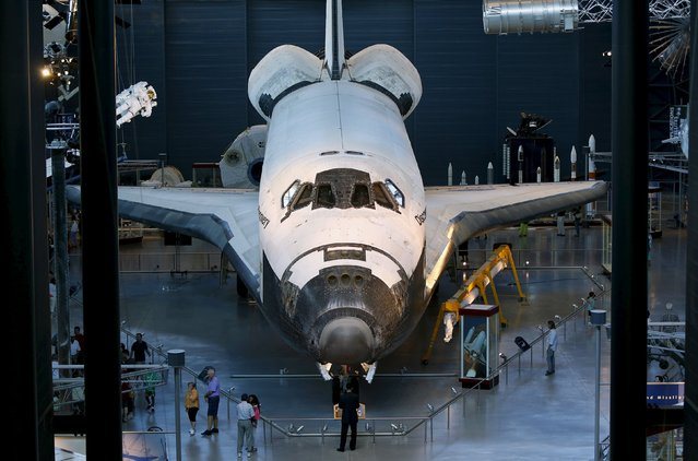 Tourists look at the space shuttle orbiter Discovery on display at the Udvar-Hazy Smithsonian National Air and Space Annex Museum in Chantilly, Virginia August 28, 2015. (Photo by Gary Cameron/Reuters)