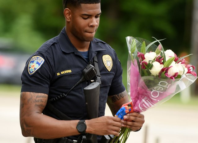 Baton Rouge Police Department Officer Markell Morris holds a bouquet of flowers and a Superman action figure that a citizen left at the Our Lady of the Lake Hospital where the police officers were brought this morning, Sunday, July 17, 2016. Multiple law enforcement officers were killed and wounded Sunday morning in a shooting near a gas station in Baton Rouge. (Photo by Henrietta Wildsmith/The Times via AP Photo)