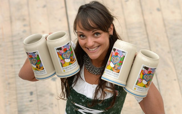 A girl presents the new Oktoberfest beer festival mug in a Oktoberfest tent in Munich, southern Germany, on August 21, 2014. The world famous beer festival Oktoberfest will takes place from September 20 to October 5, 2014. (Photo by Christof Stache/AFP Photo)