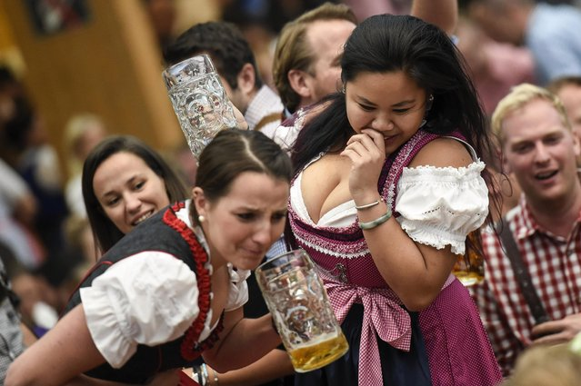 Two female revelers engage in a beer drinking contest in the Hacker Pschorr tent on the first day of the 2017 Oktoberfest beer fest on September 16, 2017 in Munich, Germany. Oktoberfest is the world's largest beer celebration and typically draws over six million visitors over its three-week run. Oktoberfest includes massive beer tents, each run by a different Bavarian brewer, as well as amusement rides and activities. (Photo by Philipp Guelland/Getty Images)