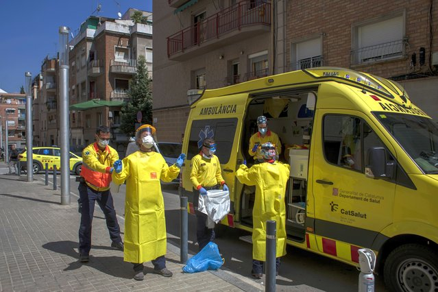 Health personnel wearing protection gear to protect against the spread of the new coronavirus prepare to attend to a patient during the COVID-19 virus outbreak in Barcelona, Spain, Monday, April 6, 2020. Spanish Prime Minister Pedro Sánchez Sánchez announced that he would ask the Parliament to extend the state of emergency by two more weeks, taking the lockdown on mobility until April 26. (Photo by Emilio Morenatti/AP Photo)