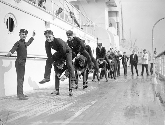 Young bellhops playing leapfrog on the sun deck of US liner Leviathan (former Hamburg America line vessel Vaterland), on arrival at Southampton, 1923. (Photo by A. R. Coster)