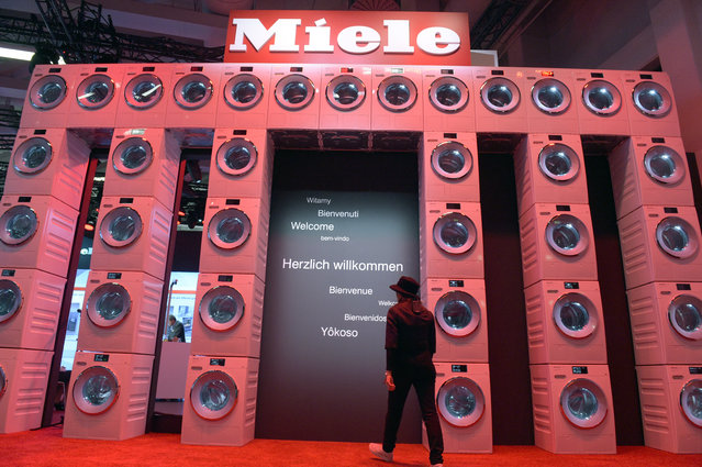 A woman walks underneath an installation of washing machines, at the trade fair stand of German electrical appliance manufacturer Miele to the International Consumer Electronics Fair IFA in Berlin, Germany, September 2, 2015. The fair will take place from 4 to 9 September 2015. (Photo by Rainer Jensen/EPA)