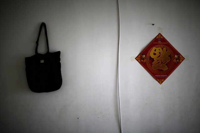 Dai Shuqin' bag (L), which was a gift from her missing younger sister a long time ago, is hung on a wall for a photograph during an interview with Reuters in Beijing July 22, 2014. Dai's sister's whole family was onboard Malaysia Airlines Flight MH370 which disappeared on March 8, 2014. Dai said she cannot go out without the bag these days because this bag makes her feel her sister is by her side when she carries the bag. (Photo by Kim Kyung-Hoon/Reuters)