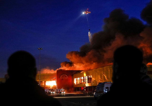 People watch as a helicopter dumps water on a fire at a construction goods market on the northwestern edge of  Moscow, Russia October 8, 2017. (Photo by Maxim Shemetov/Reuters)