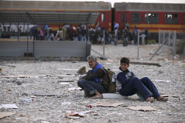 Migrants sit on the ground in a temporary camp while others board trains near Gevgelija, Macedonia, September 7, 2015. (Photo by Stoyan Nenov/Reuters)