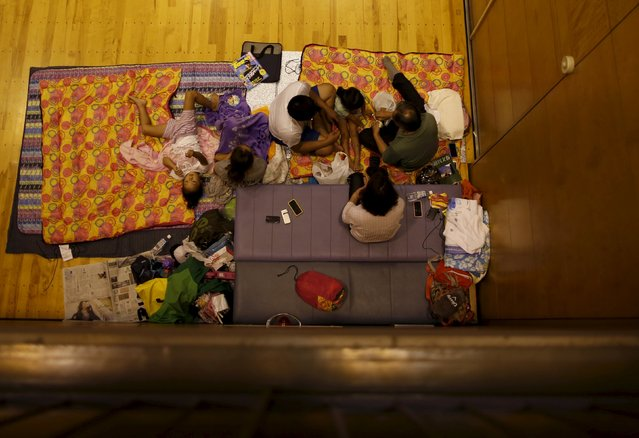 Evacuees from an area flooded by the Kinugawa river, caused by typhoon Etau, take a rest at Ishige Sports Park acting as an evacuation center in Joso, Ibaraki prefecture, Japan, September 10, 2015. (Photo by Issei Kato/Reuters)