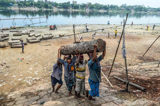 Labourers carry a log above their head near the Buriganga River in Dhaka on May 6, 2020. (Photo by Munir Uz Zaman/AFP Photo)