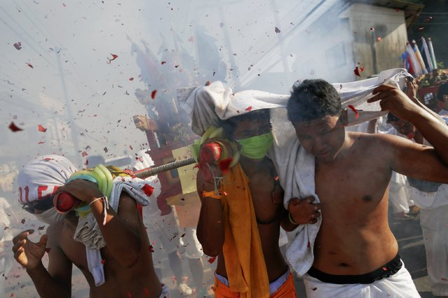 Devotees of the Ban Tha Rua Chinese shrine react amidst exploding firecrackers during a procession celebrating the annual vegetarian festival in Phuket September 28, 2014. (Photo by Damir Sagolj/Reuters)