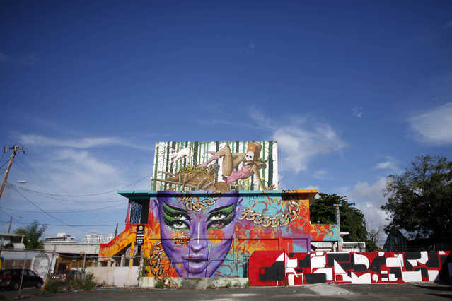 This September 22, 2014 photo, shows a building with street art murals in the Santurce neighborhood in San Juan, Puerto Rico. In Santurce, new businesses including cafes, vintage boutiques, restuarants and a bookstore are opening. The renaissance also features an arts festival that draws artists and tourists from around the world. (Photo by Ricardo Arduengo/AP Photo)