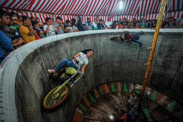 """A picture made available on 16 August 2016 shows a young dare devil motorbike rider, Karmila Purba, 18, riding her motorbike as spectators watching inside a barrel locally known as """"Tong Setan"""" or Davil's Barrel, at a traditional night carnival in Deliserdang, North Sumatra, Indonesia, 13 August 2016. (Photo by Dedi Sinuhaji/EPA)"""