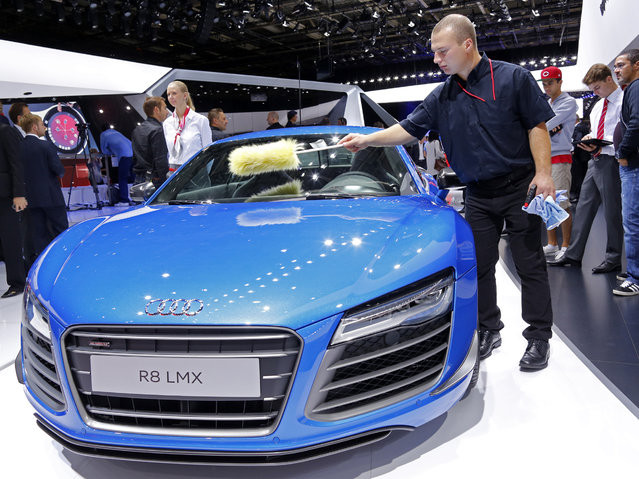 A worker cleans an Audi R8 LMX displayed on media day at the Paris Mondial de l'Automobile, October 2, 2014. (Photo by Jacky Naegelen/Reuters)