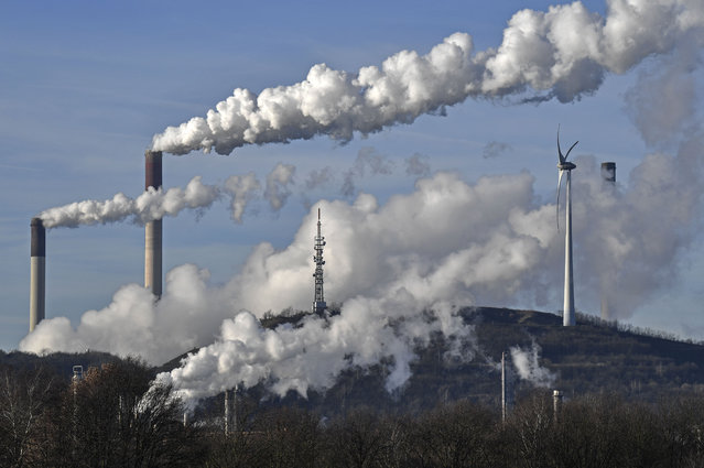 This January 16, 2020 file photo shows a Uniper energy company coal-fired power plant and a BP refinery beside a wind generator in Gelsenkirchen, Germany. The world hit another new record high for heat-trapping carbon dioxide in the atmosphere, despite reduced emissions because of the coronavirus pandemic, scientists announced Thursday, June 4, 2020. (Photo by Martin Meissner/AP Photo)