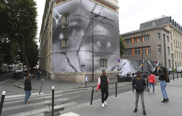 Children stand by an artwork by French street artist JR to pay homage to Adama Traore, Tuesday, June 9, 2020 in Paris. George Floyd's death have revived anger in France over police violence, systemic racism and the complicated case of Adama Traore, a black Frenchman who died in police custody in 2016. (Photo by Thibault Camus/AP Photo)