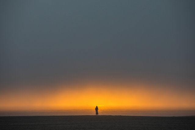 """A woman watches the sunset from the beach in Venice, California on April 26, 2020. Los Angeles County beaches are still off limits under Los Angeles county's """"Safer at Home"""" order scheduled to be enforced through at least May 15 amid the novel coronavirus pandemic. (Photo by Apu Gomes/AFP Photo)"""