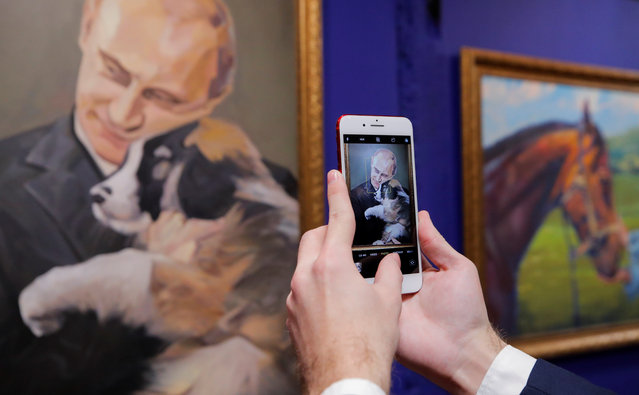 """A man takes a picture of a painting depicting Russian president Vladimir Putin at the """"SUPERPUTIN"""" exhibition at UMAM museum in Moscow, Russia on December 6, 2017. (Photo by Maxim Shemetov/Reuters)"""