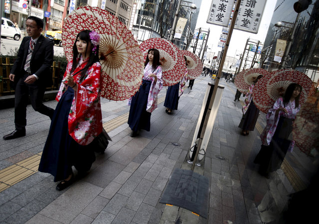 Women in Kimono holding an umbrella walk on a street at Ginza shopping district in Tokyo, Japan, March 31, 2016. (Photo by Yuya Shino/Reuters)