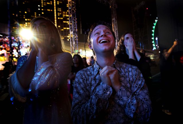 Performers react as fireworks explode over the Singapore financial district to mark the start of the new year. (Photo by Wong Maye-E/Associated Press)