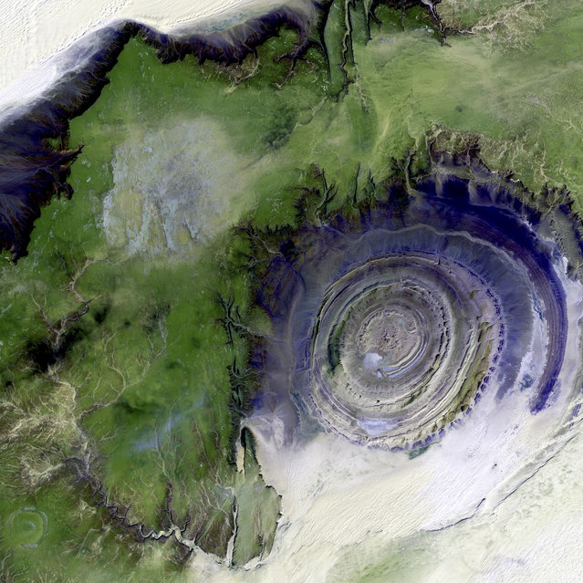 Richat Structure, Mauritania. The so-called Richat Structure is a geological formation in the Maur Adrar Desert in the African country of Mauritania. Although it resembles an impact crater, the Richat Structure formed when a volcanic dome hardened and gradually eroded, exposing the onion-like layers of rock. This image was acquired on January 11, 2001, by Landsat 7′s Enhanced Thematic Mapper plus (ETM+) sensor. This is a false-color composite image made using shortwave infrared, infrared, and green wavelengths, and has been sharpened using the sensor's panchromatic band. (Photo by NASA/GSFC/USGS EROS Data Center)