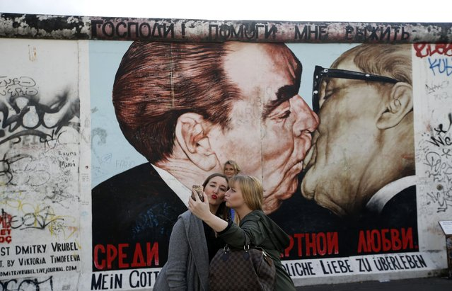 Tourists take pictures with a mobile phone in front of a painting depicting former Soviet leader Leonid Brezhnev kissing his East German counterpart Erich Honecker (R) painted on a segment of the East Side Gallery, the largest remaining part of the former Berlin Wall, in Berlin, October 15, 2014. Germany will celebrate the 25th anniversary of the fall of the wall on November 9. (Photo by Fabrizio Bensch/Reuters)