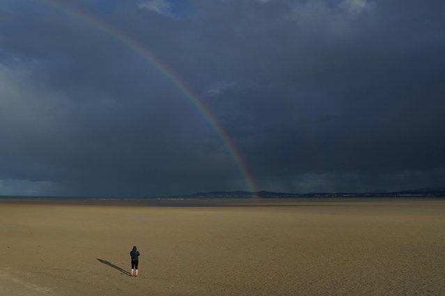 A person looks at the rainbow and heavy rain from a distance while walking along an empty beach in sunshine, following the outbreak of the coronavirus disease (COVID-19), in Dublin, Ireland, June 5, 2020. (Photo by Clodagh Kilcoyne/Reuters)