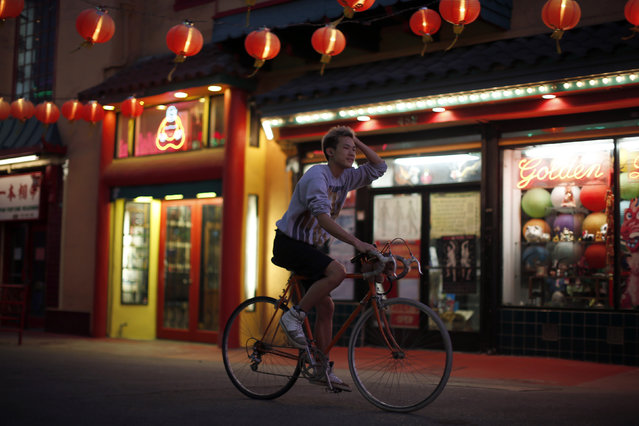 A man cycles through Chinatown in Los Angeles, California August 13, 2014. (Photo by Lucy Nicholson/Reuters)