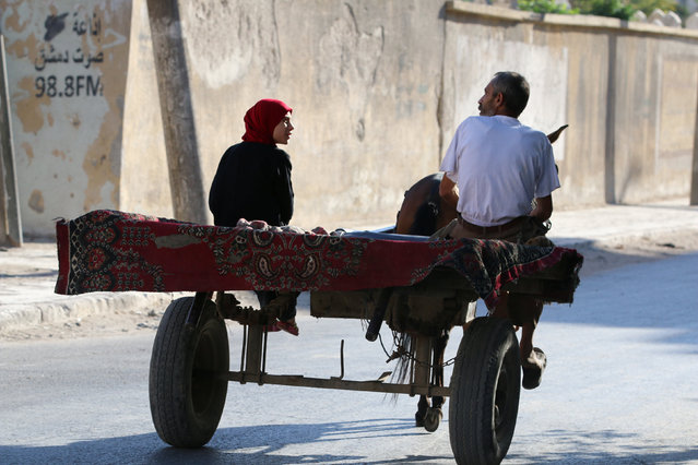 A man and a woman ride a cart in the rebel held al-Maadi district of Aleppo, Syria, August 31, 2016. (Photo by Abdalrhman Ismail/Reuters)
