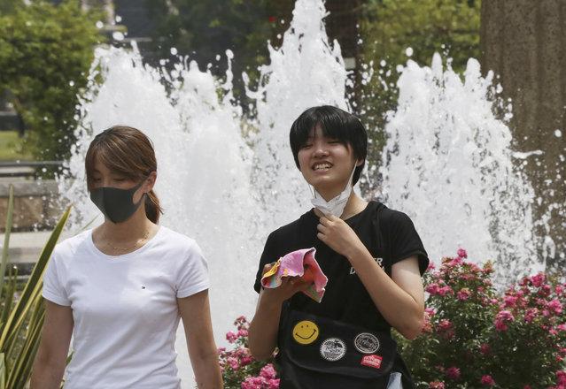 People wearing face masks to protect against the spread of the new coronavirus walk at park in Yokohama near Tokyo, Monday, August 10, 2020. (Photo by Koji Sasahara/AP Photo)