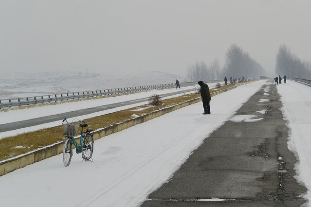 Residents walk along the streets of the snow-covered capital in February 2013, in Pyongyang, North Korea. (Photo by Andrew Macleod/Barcroft Media)