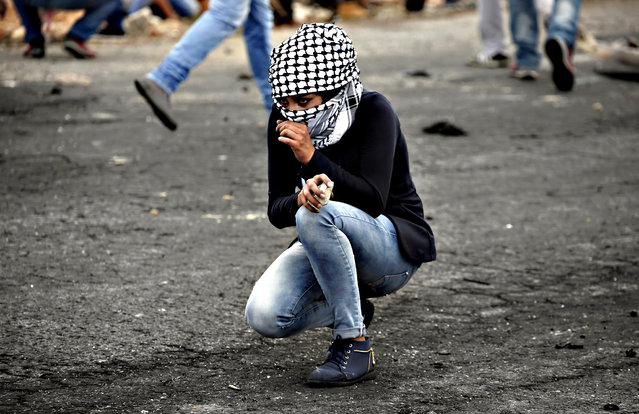 A Palestinian young woman from the Birzeit University looks on during clashes with Israeli security forces in Beit El, on the outskirts of the West Bank city of Ramallah, on October 7, 2015. New violence rocked Israel and the Israeli-occupied West Bank, including a stabbing in annexed east Jerusalem, even as Israel and Palestinian president Mahmud Abbas took steps to ease tensions. (Photo by Abbas Momani/AFP Photo)