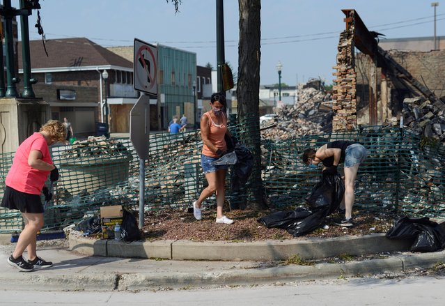 People clean up debris from a building destroyed in the fallout from protests after Jacob Blake was shot by police in Kenosha, Wisconsin, U.S. August 26, 2020. (Photo by Stephen Maturen/Reuters)