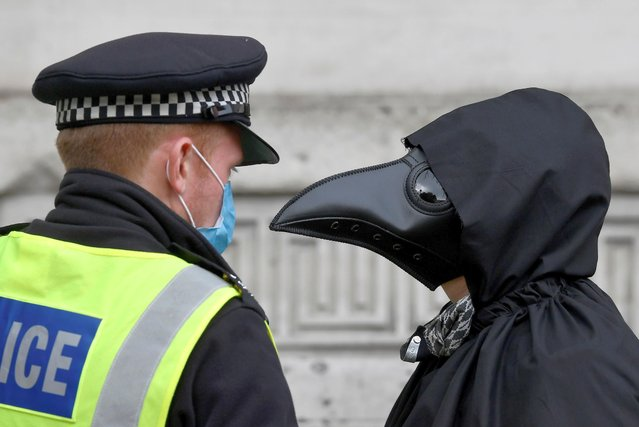 A police officer talks to the member of the Animal Rebellion group dressed in a costume as they march during an Extinction Rebellion protest in London, Britain, September 8, 2020. (Photo by Toby Melville/Reuters)