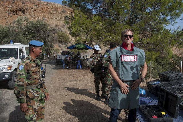 British actor Daniel Craig (R), a UN advocate against use of landmines and explosives, gets a  briefing from Cambodian de-miners at an active minefield in Cyprus, October 12 2015. His James Bond character might blow things up and kill for a living, but actor Craig was in Cyprus on Tuesday to see first hand the perils of unexploded ordnance littering the ethnically-split island. (Photo by Reuters/UN)