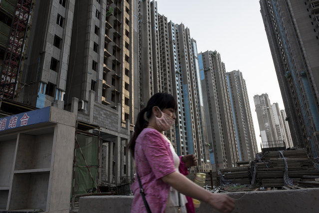 A woman walks past a massive new residential complex under construction in Yanjiao, a rapidly expanding satellite city of over 700,000 people, outside Beijing, on May 21, 2016. The complex is made up of over a dozen towers standing 34 floors high. (Photo by Michael Robinson Chavez/The Washington Post)